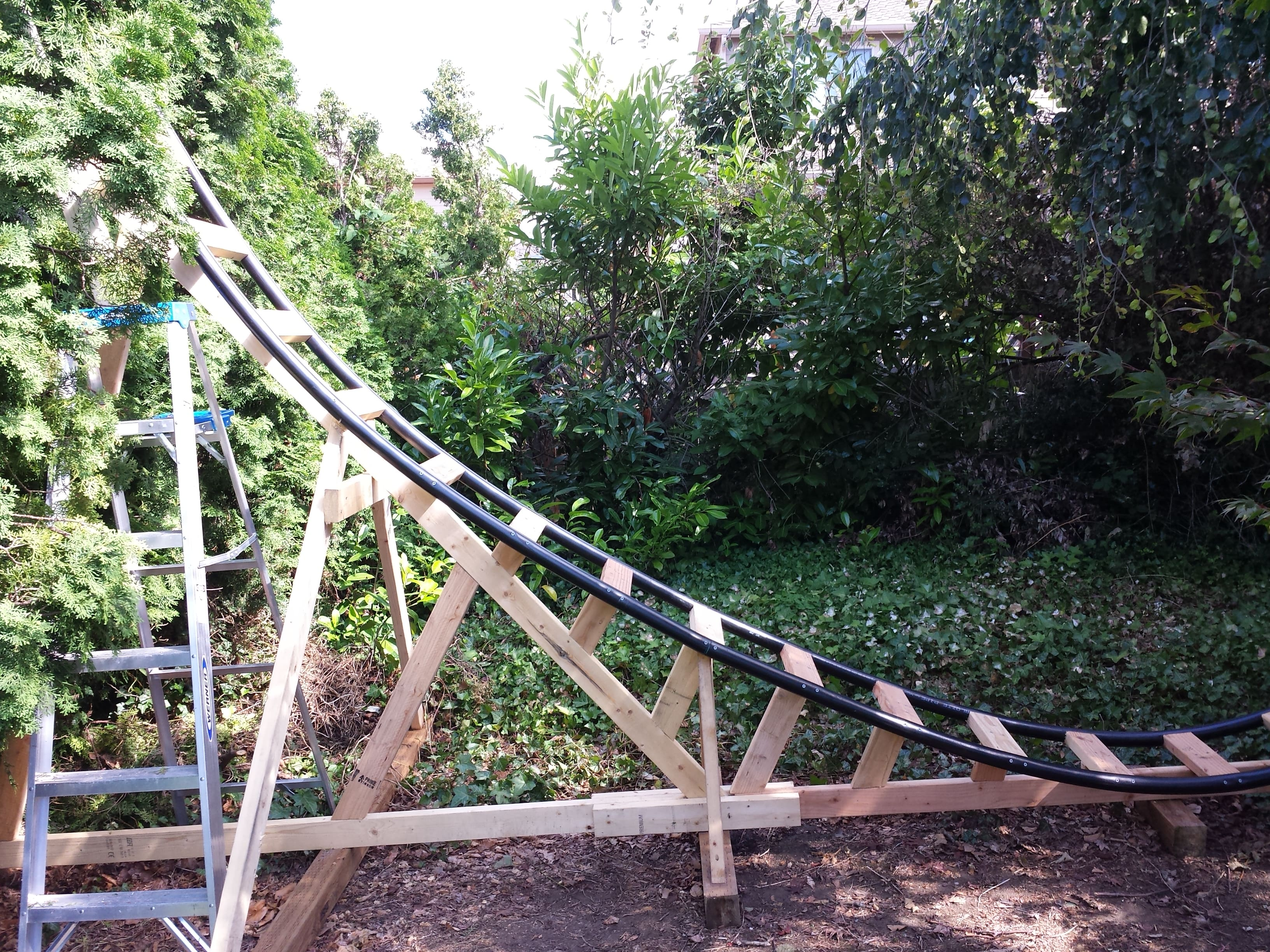 engineer builds a backyard roller coaster for his grandchildren